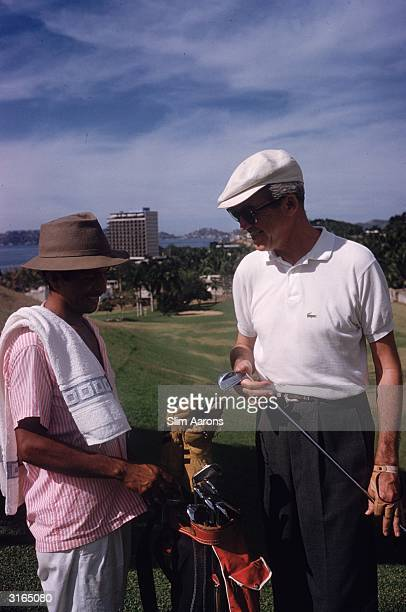 Film star James Stewart on the golf course at Acapulco Mexico consults with his caddie