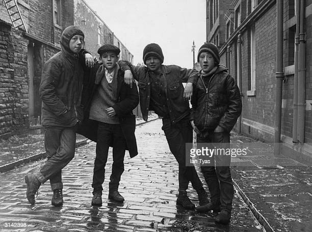 Four young lads in an cobbled alley between the old back to back terrace houses in Burnley Lancashire