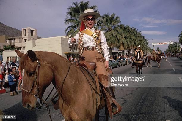 Hungarian actress Eva Gabor takes part in a rodeo parade through Palm Springs California