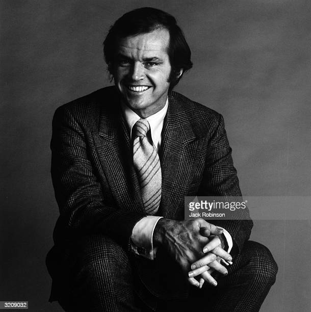 Studio portrait of American actor Jack Nicholson, crouching and smiling with his fingers intertwined.