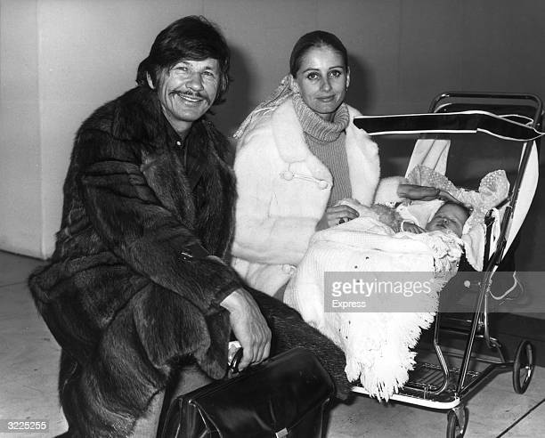 American actor Charles Bronson and his wife British actor Jill Ireland smile while posing with their young daughter Zuleika who sleeps in her baby...