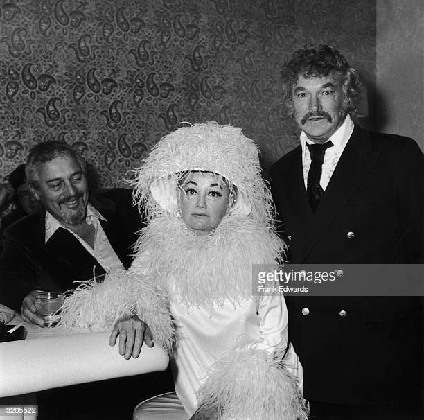 American comedian Phyllis Diller sits at a bar while her husband actor Warde Donovan stands beside her at her opening at the Riviera Hotel Las Vegas...