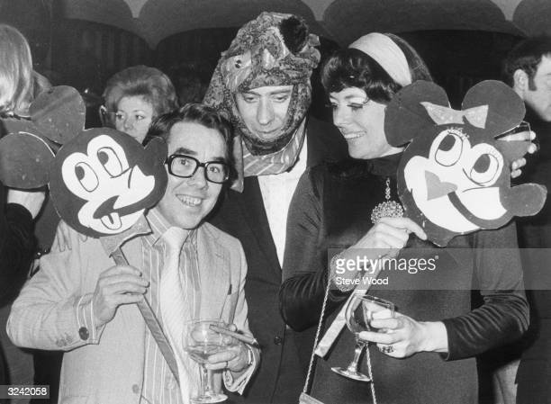 From left to right comedian Ronnie Corbett actor Victor Spinetti and Corbett's wife Anne Hart at a party Corbett and Hart are holding Mickey Mouse...