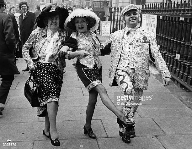 Grace and John Smith the Pearly King and Queen of South London seen here with Monica Rose the Princess of Battersea and Lambeth dancing down the...