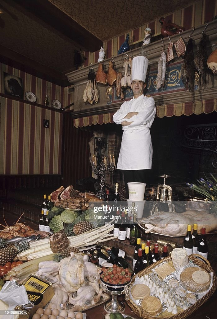 January 1973, the great chef Paul Bocuse at his restaurant 'L'Auberge du Pont de Collonges' has Collonges-au-Mont-d'Or. Cap of the hat, he poses behind a table covered with his specialties.