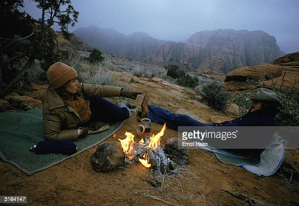 Robert Redford and Jane Fonda relax by a campfire in Utah on the set of 'The Electric Horseman', a western romance directed by Sydney Pollack.