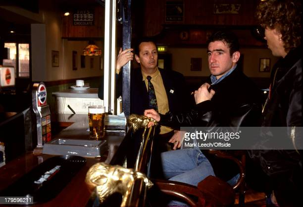 January 1992 - Eric Cantona arrives for a trial at Sheffield Wednesday Football Club - Cantona sits on a bar stool with a pint of beer in front of...
