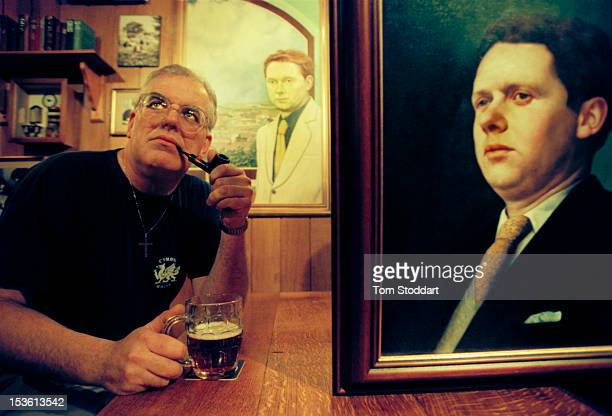 In the bar of the Black Lion Hotel in New Quay Wales a man a man enjoys a pipe and a pint of beer alongside portraits of Welsh poet and writer Dylan...