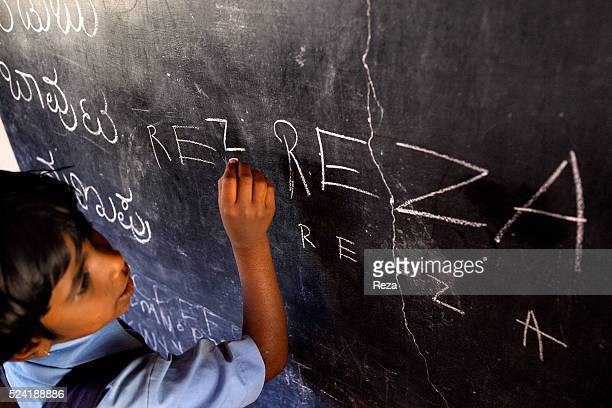January 2013 Chickmagalur India Portrait of a student writing on the blackboard the name of the photographer 'Reza' Farms connected with the...