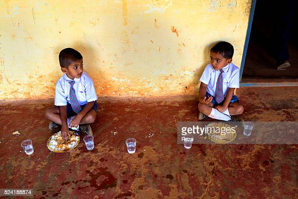 January 2013 Chickmagalur India Students in uniform eat sitting on the floor at the entrance to the classroom Farms connected with the Nespresso AAA...