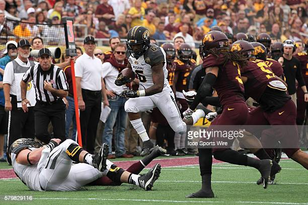 Missouri Tigers running back Marcus Murphy attempts to leap over Missouri Tigers offensive lineman Evan Boehm and Minnesota Golden Gophers defensive...