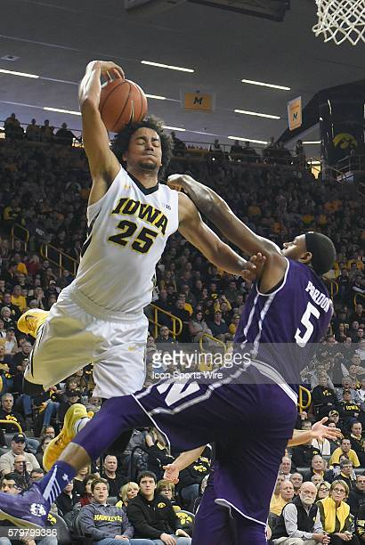 Iowa Hawkeyes forward Dom Uhl tries to hang on to the ball as he takes a shot over Northwestern center Dererk Pardon during a Big Ten Conference mens...