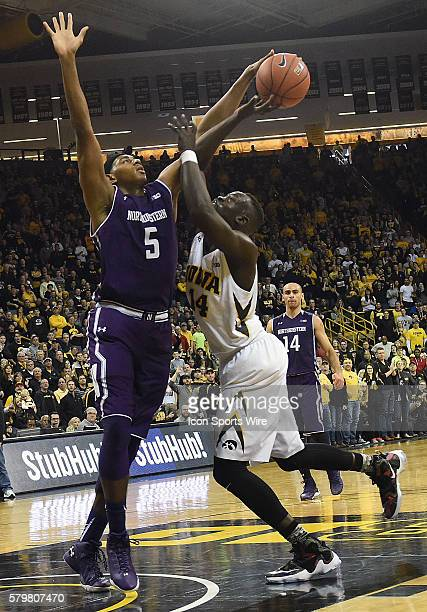 Northwestern center Dererk Pardon tries to block a shot by Iowa Hawkeyes guard Peter Jok during a Big Ten Conference mens basketball game between the...