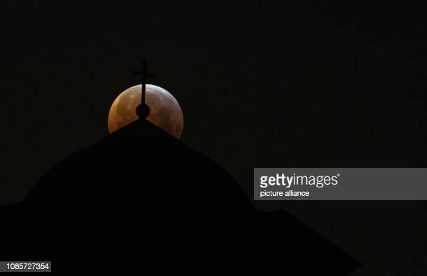 21 January 2019 BadenWuerttemberg Stuttgart The moon stands as 'blood moon' during a lunar eclipse over the funeral chapel Photo Sebastian Gollnow/dpa