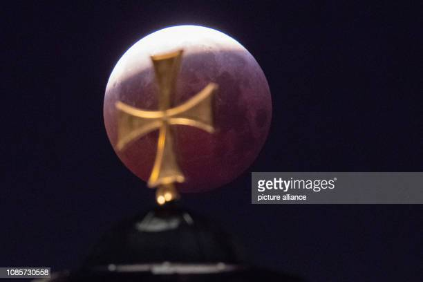 As a red socalled 'blood moon' the full moon stands over the dome of the church St Elisabeth while it steps out of the shadow of the earth Photo...
