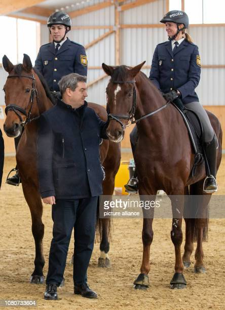 Markus Söder Prime Minister of Bavaria is next to the police riders Robin Philipp with horse Hermes and Stephanie Sendker with horse Noris at the...