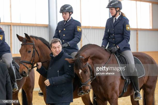 Markus Söder Prime Minister of Bavaria stands next to the police riders Robin Philipp with horse Hermes and Stephanie Sendker with horse Noris at the...