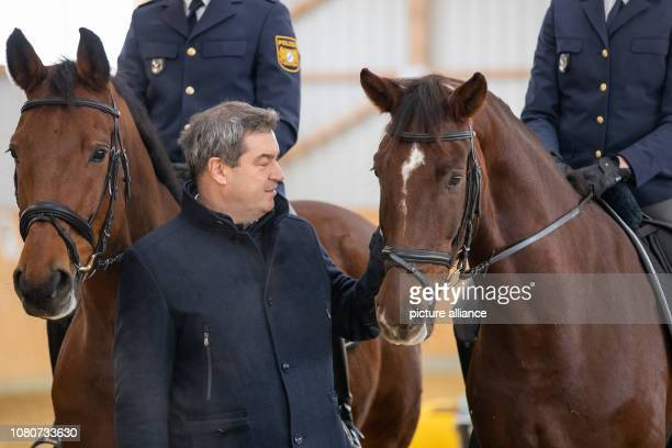 Markus Söder Prime Minister of Bavaria stands next to the horses of the riding group of the Middle Franconian police Hermes and Noris at the...