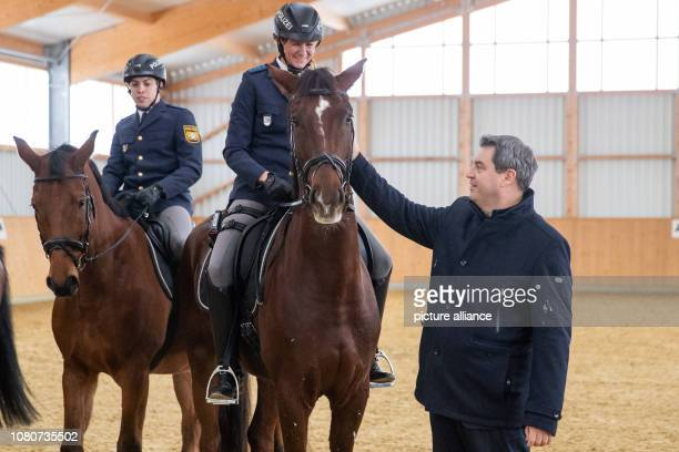 Markus Söder Prime Minister of Bavaria stands next to the police riders Robin Philipp with horse Hermes and Stephanie Sendker with horse Noris The...