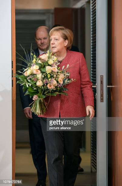Chancellor Angela Merkel arrives with a bouquet of flowers before Olaf Scholz Federal Minister of Finance at the Federal Cabinet meeting at the...