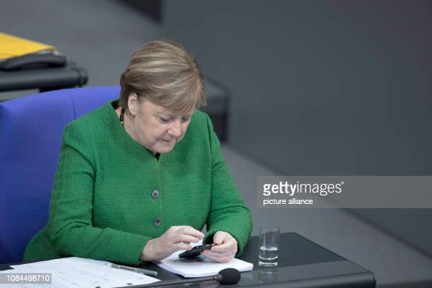 Chancellor Angela Merkel sits in the plenary session of the German Bundestag and looks at her smartphone The main topics of the 74th session of the...