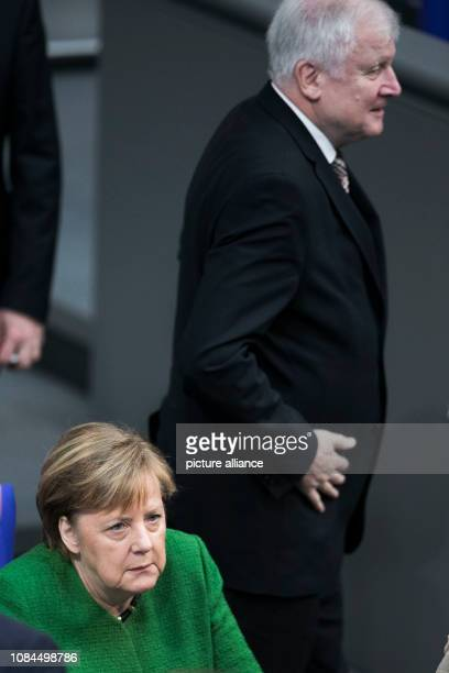 Horst Seehofer Federal Minister of the Interior Building and Home Affairs passes behind Chancellor Angela Merkel in the plenary session of the German...