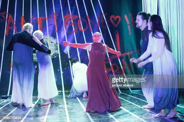 The actress Zora Schemm dressed in red and other actors stand on the stage of the Deutsches Theater during the photo rehearsal of the play 'Antigone'...