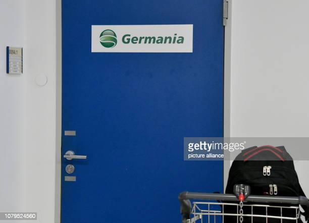 A baggage car stands in front of a locked door with the Germania logo at Schoenefeld Airport After the turbulent flight summer of 2018 the airline...