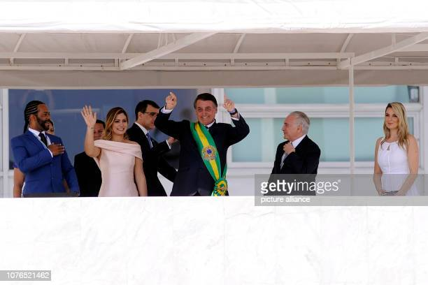 Brazil's new president Jair Bolsonaro waves to the crowd from the Planalto presidential palace Next to him are his wife Michelle Bolsonaro and the...