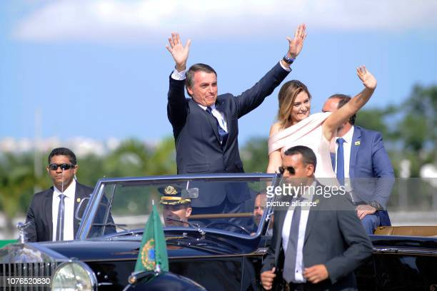 Brazil's President Jair Bolsonaro waves while he and his wife Michelle drive through the capital Brasilia in an open Rolls Royce The ultraright...