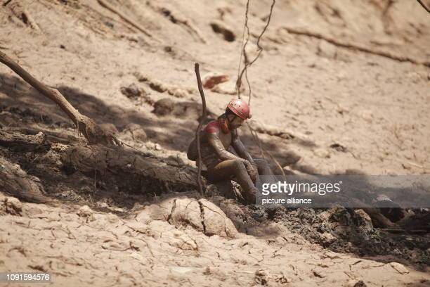 A firefighter sits full of mud and cries at the edge of the rescue work after the dam burst at an iron ore mine on After the dam burst a mud...