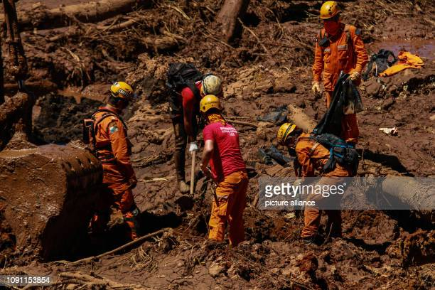 Helpers search the mud for victims and possibly survivors The dams of a retention basin at the Córrego do Feijão iron ore mine were broken on Friday...