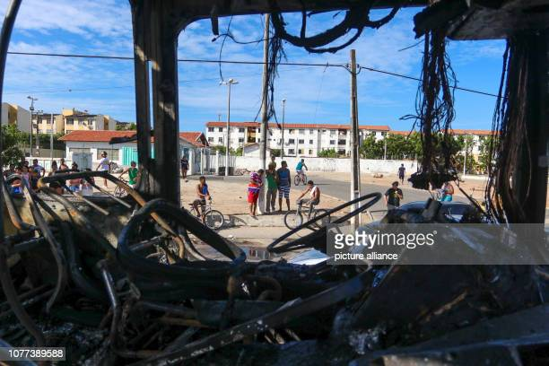 January 2019, Brazil, Fortaleza: People look at the remains of a burned-out vehicle after an attack in Fortaleza. The newly inaugurated Brazilian...
