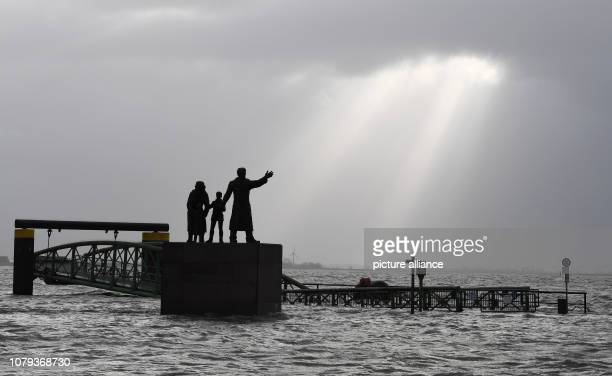 Sunrays break through the clouds at the emigrant memorial on the flooded WillyBrandPlatz Storm 'Benjamin' rages on the German coasts Experts warn...
