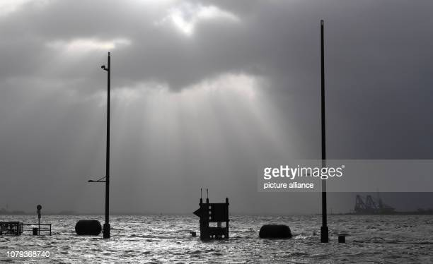 Sunrays break through the clouds at the flooded WillyBrandPlatz Storm 'Benjamin' rages on the German coasts Experts warn against a storm surge in...