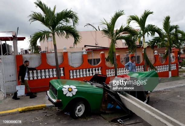 Cubans walk in Guanabacoa next to a destroyed car after a tornado has wreaked havoc A violent tornado on Cuba on Sunday evening cost at least three...
