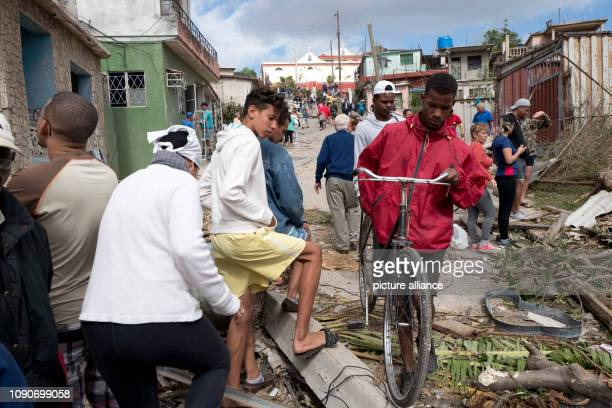 Cubans walk the streets of Regla after a tornado caused devastation A violent tornado on Cuba on Sunday evening cost at least three people their...