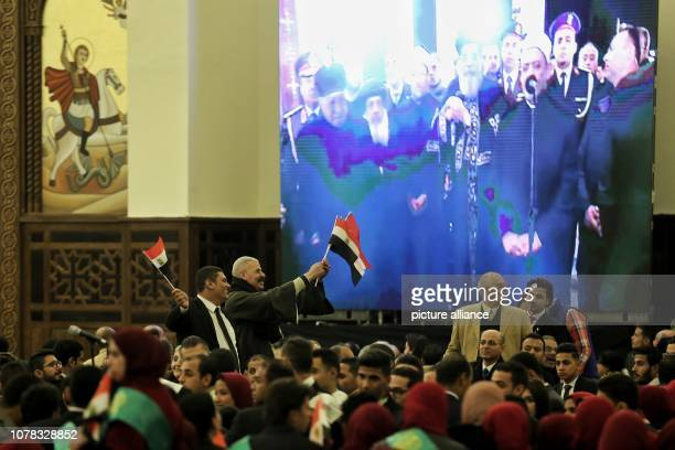 Egyptians wave flags while Pope Tawadros II of Alexandria and Patriarch of the See of St Mark and Azhar Grand Imam Ahmed alTayeb can be seen on a...