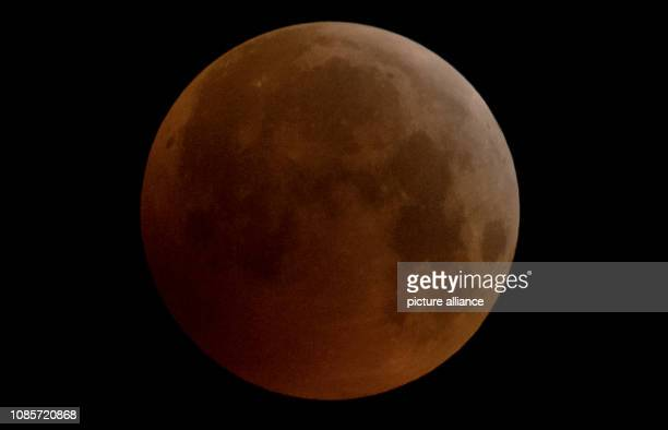 As a red socalled 'blood moon' the full moon presents itself over Frankfurt while it steps into the core shadow of the earth illuminated by the sun...