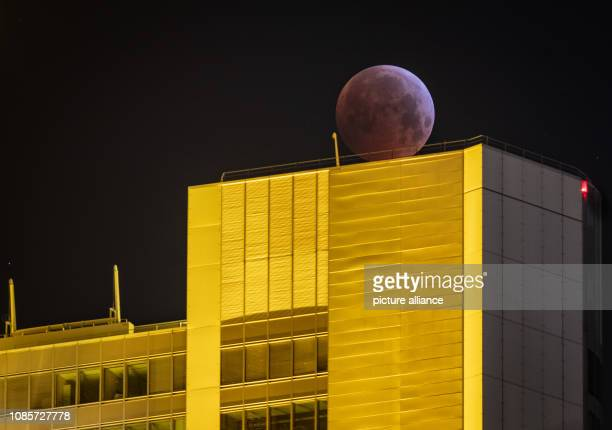 As a red socalled 'blood moon' the full moon stands over the yellow illuminated Commerbank headquarters while it steps into the shadow of the earth...