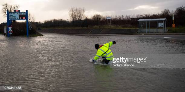 During the storm a worker walks along the flooded area of the ferry port on the North Sea island of Borkum Photo Mohssen Assanimoghaddam/dpa