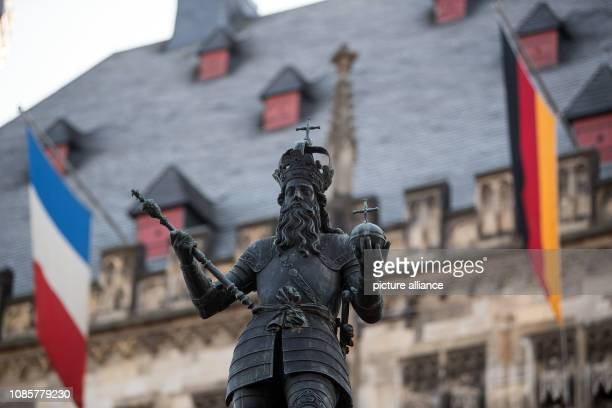 21 January 2019 North RhineWestphalia Aachen A German and a French flag hang behind the figure of Charlemagne at the town hall Chancellor Merkel and...