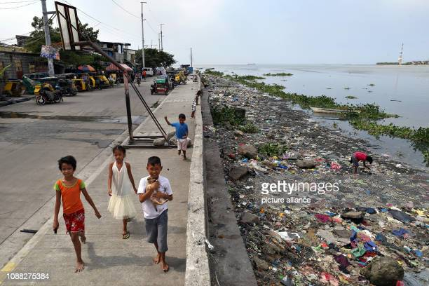 Several children walk along the heavily polluted shore in Manila Bay The Philippine government will begin remediation work on 27 January in Manila...