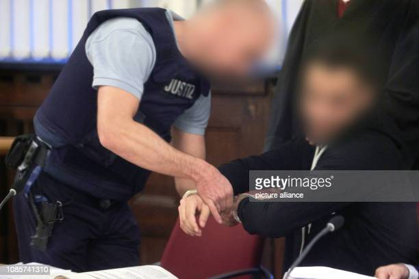 21 January 2019 RhinelandPalatinate Koblenz A prison officer removes the handcuffs from the 23yearold defendant in the courtroom of the Higher...