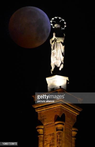 21 January 2019 RhinelandPalatinate Trier The reddish shimmering full moon a socalled 'blood moon' stands behind the Mariensäule in Trier Photo...