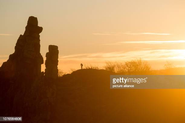 03 January 2019 SaxonyAnhalt Neinstedt The sun rises behind the Harz mountains while a photographer positions his camera in front of the rocks of the...
