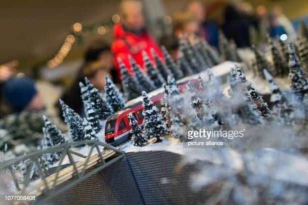 The model of a regional train of Deutsche Bahn with gauge H0 runs through a snowcovered model landscape The winter landscape was built by the working...