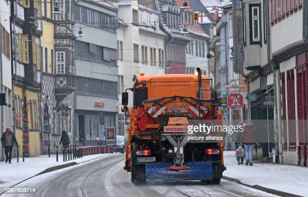 January 2019, Thuringia, Erfurt: Winter road clearance services sprinkle salt in the old town of Erfurt. Meteorologists say it will remain frosty in...