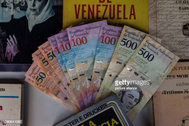 January 2019, Venezuela, Caracas: Bolivar bills are lying on a table in an antiquarian bookshop. From , the private money house Interbanex may...