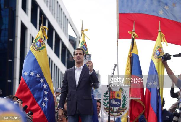 Juan Guaido president of the disempowered parliament in Venezuela declares himself head of state at a rally in front of supporters and holds a copy...
